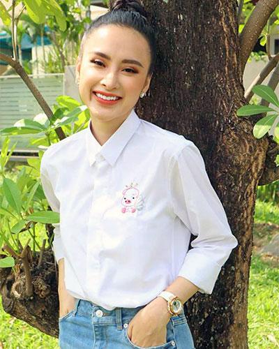 Nữ hoàng thảm đỏ nổi bật của showbiz Việt, nhưng khi tham gia các hoạt động từ thiện và các chương trình quảng cáo - cộng đồng, Angela Phương Trinh lại chọn trang phục áo mùa đông - xuân rất đơn giản. Áo sơ mi cổ bẻ màu trắng, trang trí nhấn nhẹ họa tiết biểu trưng heo hồng được cô ấy phối cùng quần jeans trẻ trung năng động